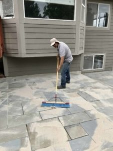 putting the finishing touches on natural stone patio installed by expert stone mason